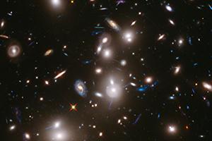 Imagem do gigantesco enxame de galáxias Abell 2744, que se situa a 3,5 mil milhões de anos-luz. A sua imensa gravidade atua como lente gravitacional, ampliando e distorcendo a imagem de galáxias de fundo, a distâncias que chegam aos 12 mil milhões de anos-luz. Crédito: NASA, ESA, J. Lotz, M. Mountain, A. Koekemoer e qeuipa HFF (STScI)