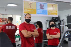 Dois instrutores com Equipamentos de proteção individual na sala de musculação e medidas de segurança para os membros