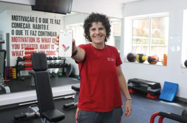 Instrutora de fitness a segurar o telemóvel com a aplicação na sala de musculação do Programa UPFit